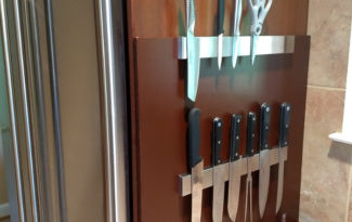 Knives and a pair of scissors on magnetic knife bars attached to a wooden mount.