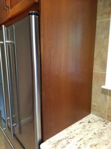 Custom cabinetry surrounding a stainless steel refrigerator.